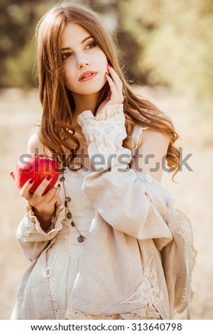 Beautiful woman clothing style boho in autumn outdoor. Woman with red apple - stock photo