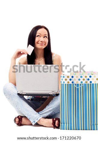 Beautiful woman contemplates her online purchase. Isolated on white.