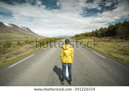 Beautiful woman contemplating a beautiful road surrounded by nature - stock photo