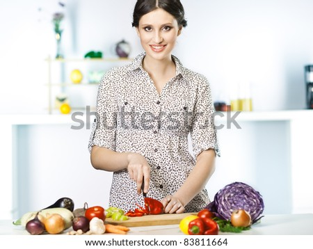 Beautiful woman cooking healthy food in the kitchen - stock photo