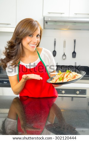 beautiful woman cooking in modern kitchen holding a plate of food. - stock photo