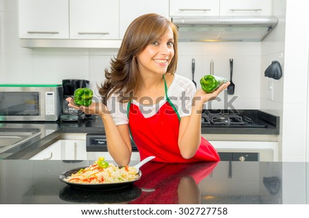 beautiful woman cooking in modern kitchen posing holding capsicum and smiling with plate of food on counter. - stock photo