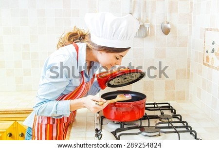 Beautiful woman cooking in the kitchen at home. - stock photo