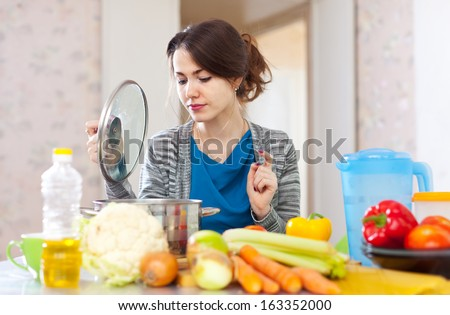 beautiful woman cooking vegetarian lunch in  kitchen  - stock photo