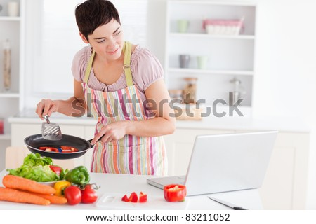 Beautiful woman cooking with receipt on laptop in the kitchen - stock photo