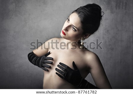 Beautiful woman covering her breasts with her hands - stock photo
