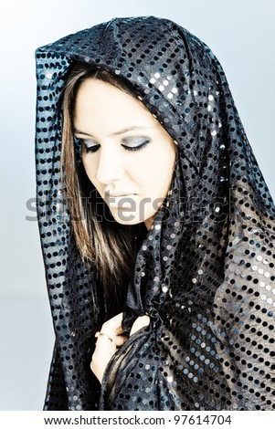 Beautiful woman  covering her face with a black hijab with beautiful bright spots on it.