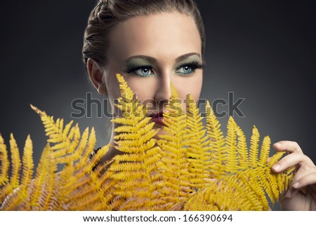 Beautiful woman covering her face with yellow leaves - stock photo