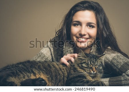 Beautiful woman cuddling a cat and smiling at camera - stock photo