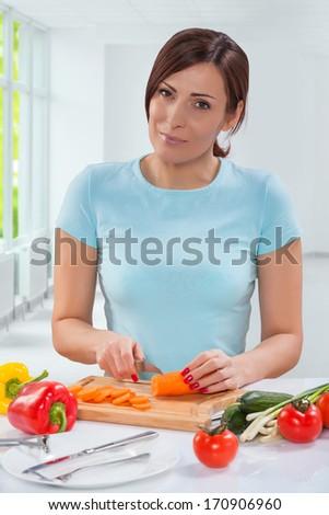 beautiful woman cutting carrot - stock photo