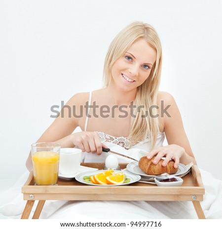 Beautiful woman cutting croissant - stock photo