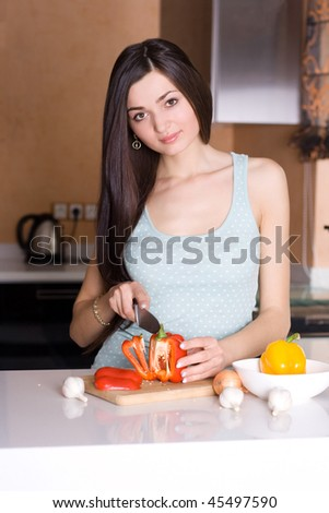 Beautiful woman cutting vegetable in the kitchen