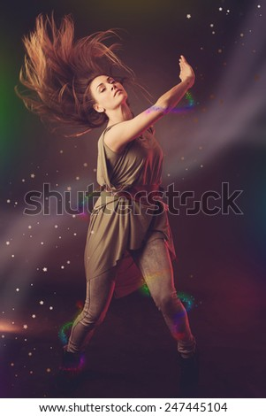 Beautiful woman dancer dancing over dark background with light rays and star swirls and glitters