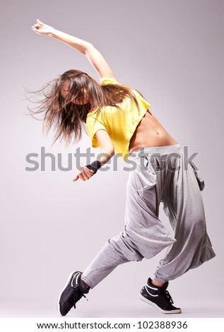 beautiful woman dancer in a passionate dance pose on gray background