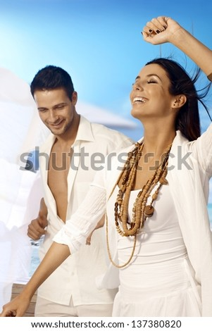 Beautiful woman dancing eyes closed on the beach, man watching. - stock photo