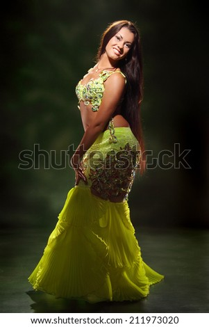 beautiful woman dancing in colorful Arabic dance costume - stock photo