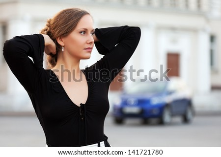 Beautiful woman daydreaming on the city street - stock photo