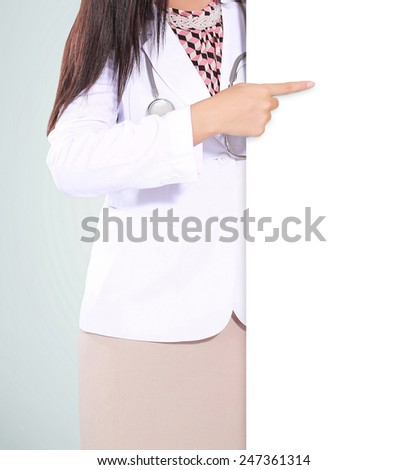 beautiful woman doctor smiling and pointing a blank board, isolated on green background - stock photo