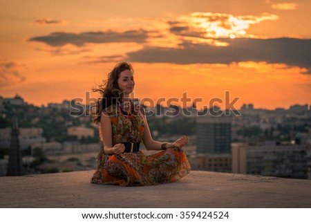 Beautiful woman doing a yoga exercise on the rooftop of a skyscraper at sunset - stock photo