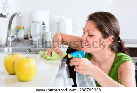 Beautiful woman doing chores around the house thoroughly cleaning furtniture in kitchen - stock photo