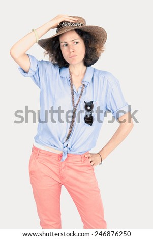 Beautiful woman doing different expressions in different sets of clothes: posing with sunglasses and a hat - stock photo