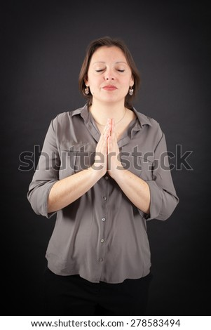 Beautiful woman doing different expressions in different sets of clothes: prayer - stock photo