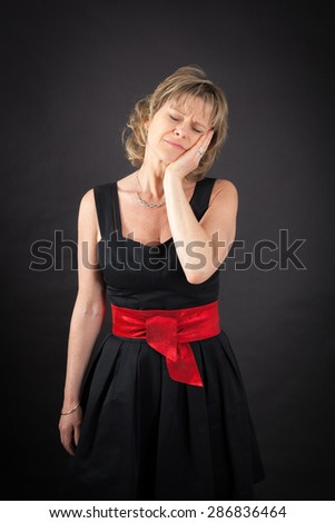 Beautiful woman doing different expressions in different sets of clothes: toothache - stock photo