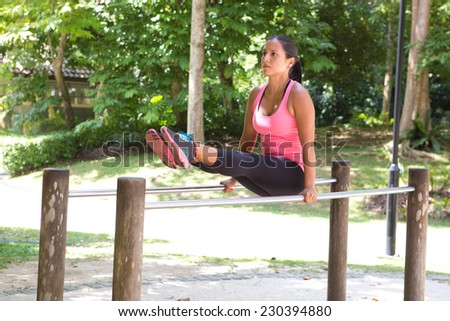 Beautiful woman doing dips exercise on balancing bar in park - stock photo