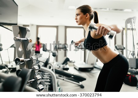 Beautiful woman doing exercise with dumbbell in gym