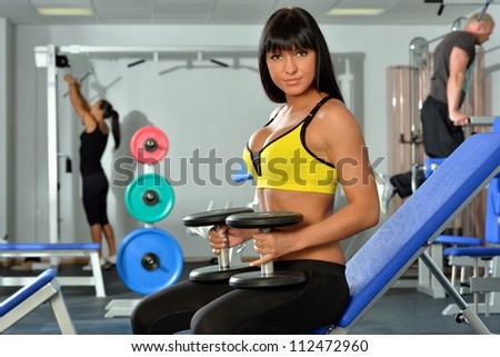 Beautiful woman doing exercises in a sport club.