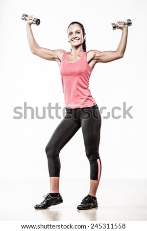 Beautiful woman doing fitness exercise with dumbbellls - stock photo