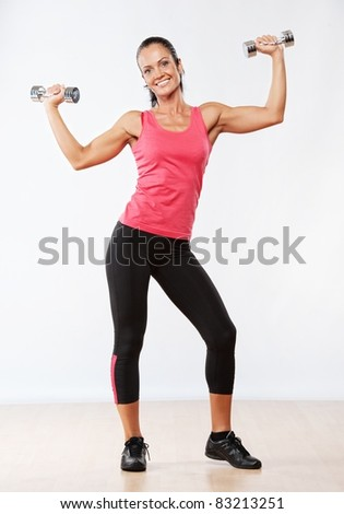 Beautiful woman doing fitness exercise with dumbbells. - stock photo