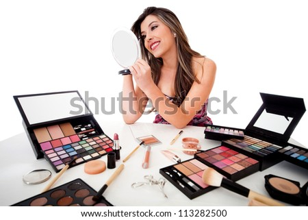 Beautiful woman doing her makeup - isolated over a white background - stock photo