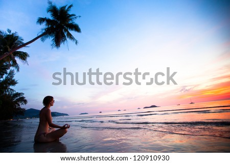 Beautiful woman doing lotus yoga pose on the beach near the ocean at sunset in Thailand - stock photo