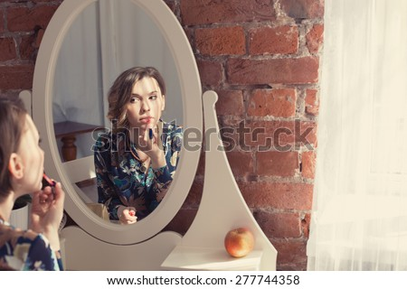 Beautiful woman doing make up and coloring her lips looking to the mirror in bedroom interior near a large window  - stock photo