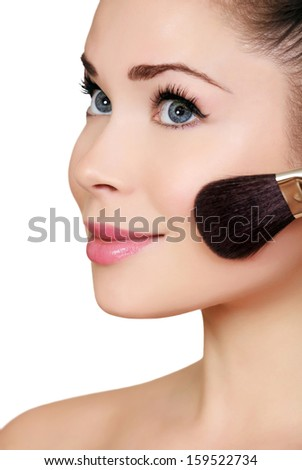Beautiful woman doing make-up on face with cosmetic brush  - stock photo