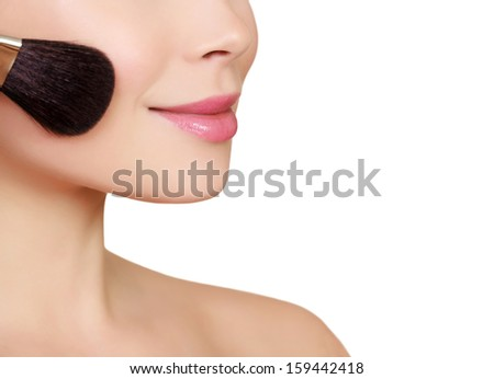 Beautiful woman doing make-up on face with cosmetic brush, copyspace  - stock photo