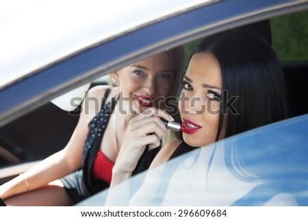beautiful woman doing makeup in the car - stock photo