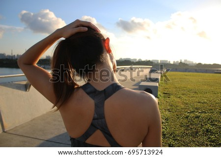 Beautiful woman doing neck stretching exercises near a park and barrage