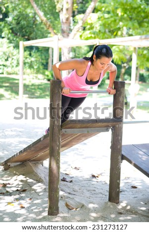 Beautiful woman doing push up on bar in outdoor exercise park