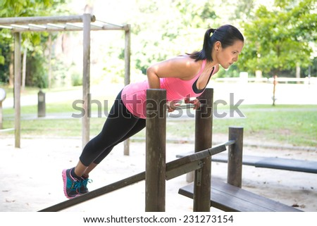 Beautiful woman doing push up on bar in outdoor exercise park - stock photo
