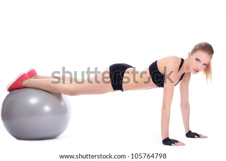 Beautiful woman doing push ups on fitness ball over white background - stock photo