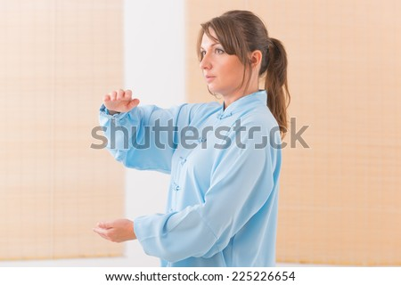 Beautiful woman doing qi gong tai chi exercise wearing professional, original Chinese clothes at gym - stock photo