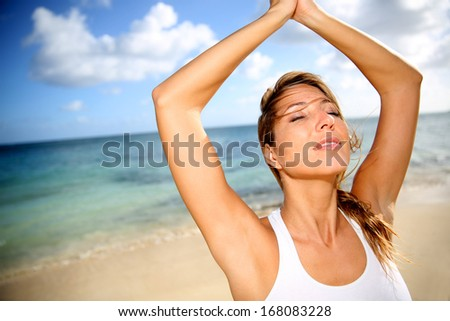 Beautiful woman doing yoga exercises on the beach