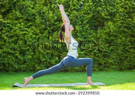 beautiful woman doing yoga on green grass in park at summer morning - stock photo