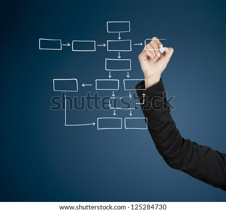 Beautiful woman drawing a diagram on glass board with a marker - stock photo
