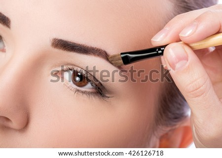 Beautiful woman drawing a shape of eyebrows using cosmetic brush. Make up artist applying make up to a model  - stock photo