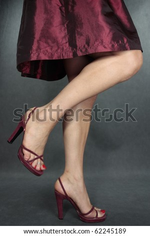 Beautiful woman dress legs red shoes  on grey