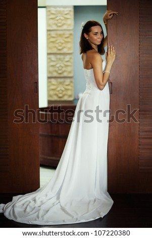 beautiful woman dressed as a bride standing next to the wood door - stock photo