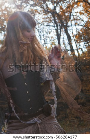 beautiful woman dressed boho style sitting on the autumn leafes
